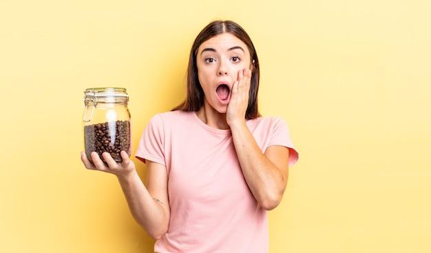 Jonge spaanse vrouw die zich geschokt en bang voelt. koffiebonen concept