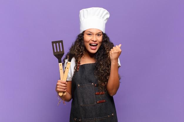 Jonge spaanse vrouw die zich geschokt, opgewonden en gelukkig voelt, lacht en succes viert, zeggend wow !. barbecue chef-kok concept