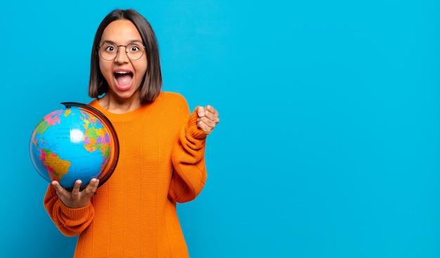 Jonge spaanse vrouw die zich geschokt, opgewonden en gelukkig voelt, lacht en succes viert
