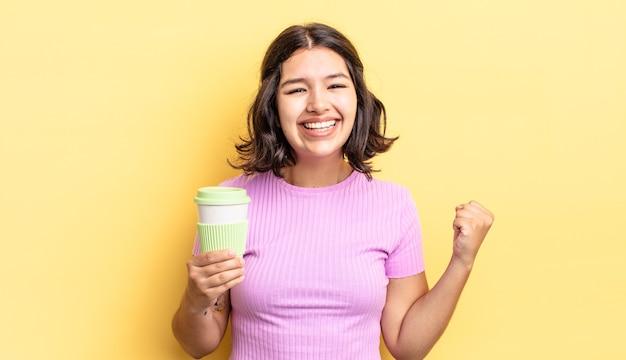 Jonge spaanse vrouw die zich geschokt voelt, lacht en succes viert. afhaal koffie concept