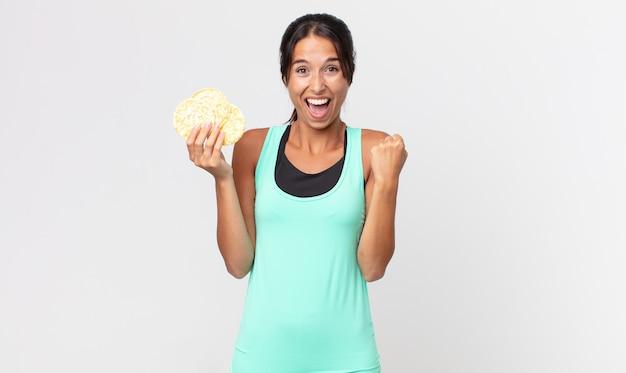 Jonge spaanse vrouw die zich geschokt voelt, lacht en succes viert. fitness dieet concept
