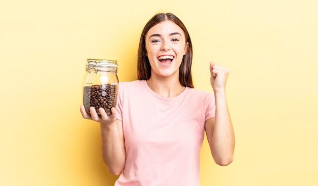 Jonge spaanse vrouw die zich geschokt voelt, lacht en succes viert. koffiebonen concept