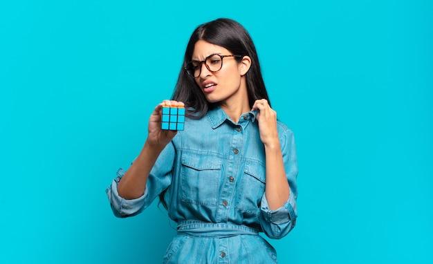 Jonge spaanse vrouw die zich gestrest, angstig, moe en gefrustreerd voelt, aan de hals van het shirt trekt, gefrustreerd kijkt door het probleem. intelligentie probleem concept