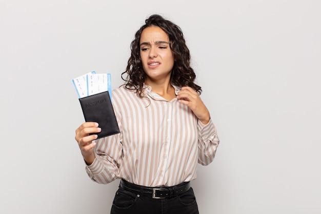 Jonge spaanse vrouw die zich gestrest, angstig, moe en gefrustreerd voelt, aan de hals van het shirt trekt, gefrustreerd kijkt door het probleem