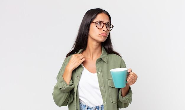 Jonge spaanse vrouw die zich gestrest, angstig, moe en gefrustreerd voelt en een koffiemok vasthoudt