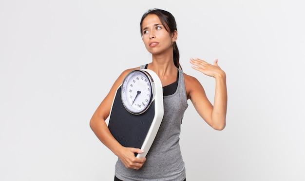 Jonge spaanse vrouw die zich gestrest, angstig, moe en gefrustreerd voelt en een weegschaal vasthoudt. dieet concept