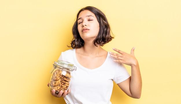 Jonge spaanse vrouw die zich gestrest, angstig, moe en gefrustreerd voelt. koekjes fles concept