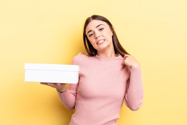 Jonge spaanse vrouw die zich gestrest, angstig, moe en gefrustreerd voelt. lege doos concept