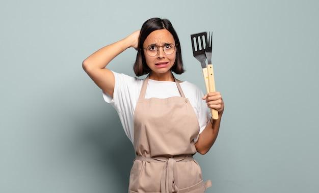 Jonge spaanse vrouw die zich gestrest, bezorgd, angstig of bang voelt, met de handen op het hoofd, in paniek bij vergissing