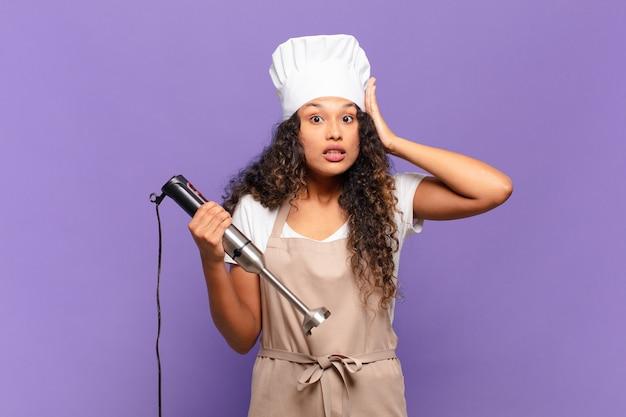 Jonge spaanse vrouw die zich gestrest, bezorgd, angstig of bang voelt, met de handen op het hoofd, in paniek per ongeluk. chef-kok concept