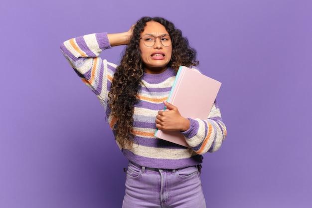 Jonge spaanse vrouw die zich gestrest, bezorgd, angstig of bang voelt, met de handen op het hoofd, in paniek per ongeluk. studentenconcept
