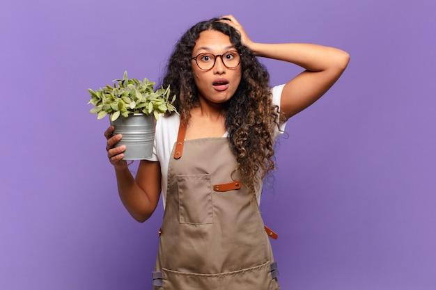 Jonge spaanse vrouw die zich gestrest, bezorgd, angstig of bang voelt, met de handen op het hoofd, in paniek per ongeluk. tuin keeper concept