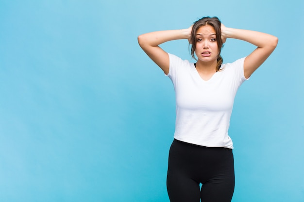 Jonge spaanse vrouw die zich gestrest, bezorgd, angstig of bang voelt, met de handen op het hoofd, in paniek raakt bij een fout
