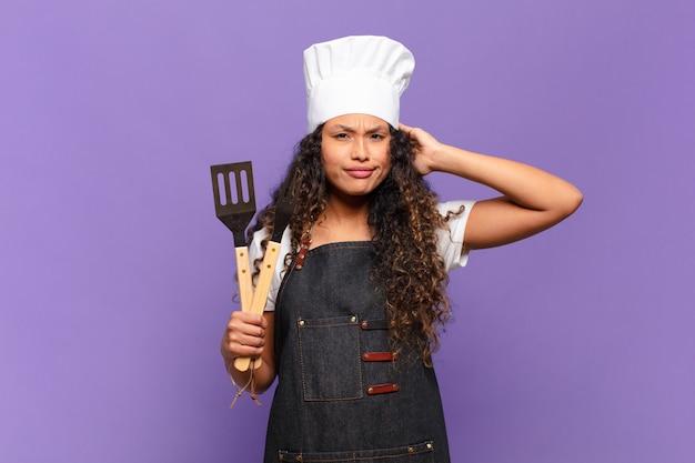 Jonge spaanse vrouw die zich gestrest, bezorgd, angstig of bang voelt, met de handen op het hoofd, in paniek raakt bij vergissing. barbecue chef-kok concept