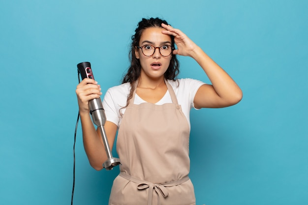 Jonge spaanse vrouw die zich gestrest, bezorgd, angstig of bang voelt, met de handen op het hoofd, in paniek raakt bij vergissing
