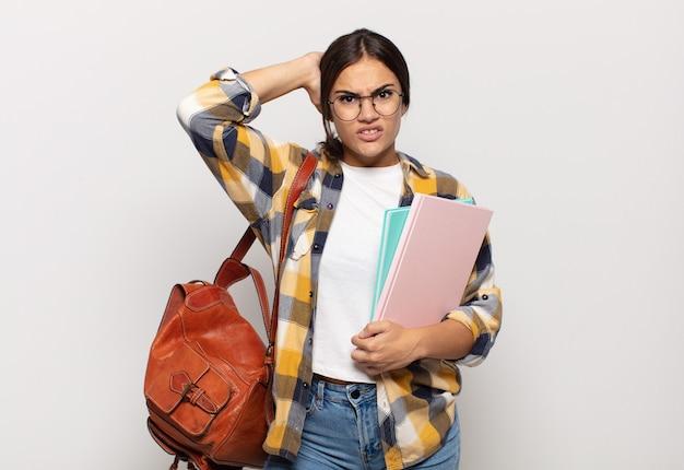 Jonge spaanse vrouw die zich gestrest, bezorgd, angstig of bang voelt, met de handen op het hoofd