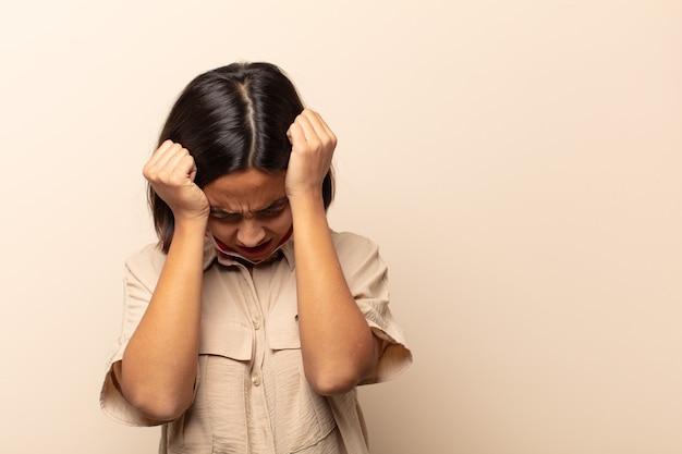 Jonge spaanse vrouw die zich gestrest en gefrustreerd voelt, handen naar het hoofd brengt, zich moe, ongelukkig en met migraine voelt