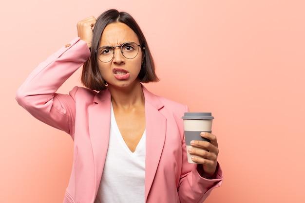 Jonge spaanse vrouw die zich gestrest en gefrustreerd voelt, handen tegen het hoofd steekt, zich moe, ongelukkig en met migraine voelt