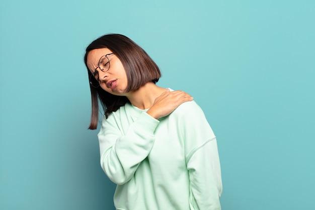 Jonge spaanse vrouw die zich moe, gestrest, angstig, gefrustreerd en depressief voelt, last heeft van rug- of nekpijn