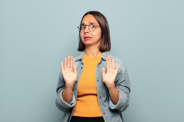 Jonge spaanse vrouw die zich stomverbaasd en bang voelt, bang is voor iets beangstigend, met de handen naar voren open en zegt: blijf weg
