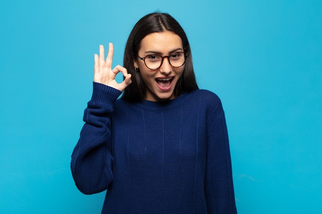 Jonge spaanse vrouw die zich succesvol en tevreden voelt, glimlachend met wijd open mond, goed teken makend met de hand