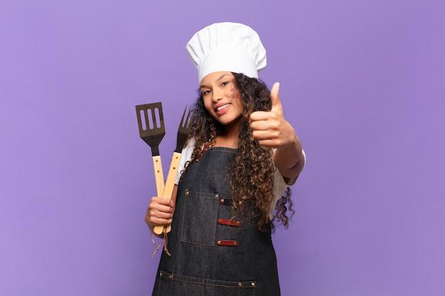 Jonge spaanse vrouw die zich trots, zorgeloos, zelfverzekerd en gelukkig voelt, positief glimlacht met omhoog duimen. barbecue chef-kok concept