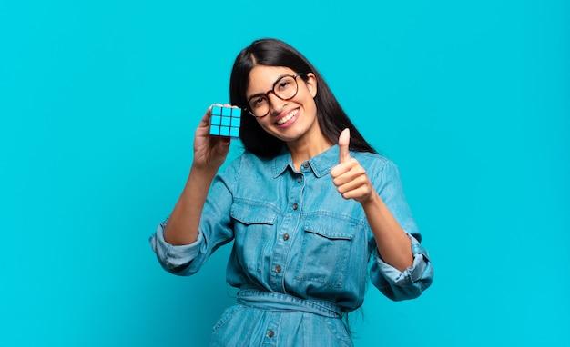 Jonge spaanse vrouw die zich trots, zorgeloos, zelfverzekerd en gelukkig voelt, positief glimlacht met omhoog duimen. intelligentie probleem concept