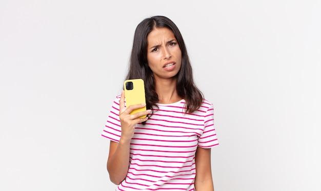 Jonge spaanse vrouw die zich verbaasd en verward voelt en een smartphone vasthoudt
