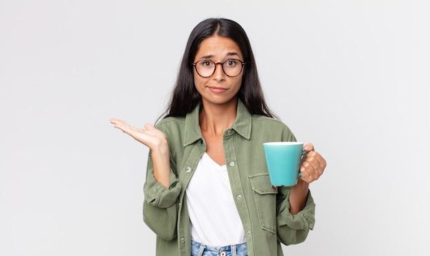 Jonge spaanse vrouw die zich verbaasd en verward voelt en twijfelt en een koffiemok vasthoudt