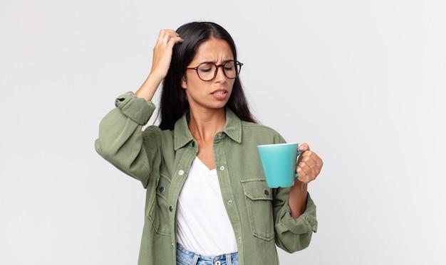Jonge spaanse vrouw die zich verbaasd en verward voelt, haar hoofd krabt en een koffiemok vasthoudt