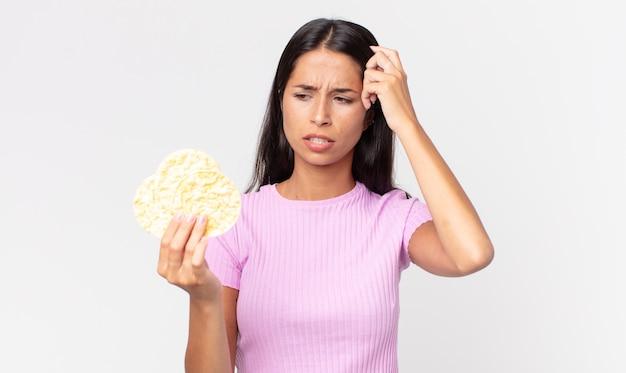 Jonge spaanse vrouw die zich verbaasd en verward voelt, haar hoofd krabt en een rijstkoekje vasthoudt. dieet concept