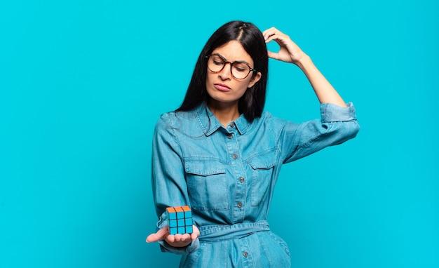 Jonge spaanse vrouw die zich verbaasd en verward voelt, haar hoofd krabt en naar de zijkant kijkt. intelligentie probleem concept