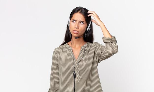 Jonge spaanse vrouw die zich verbaasd en verward voelt, hoofd krabben met een headset. telemarketing concept