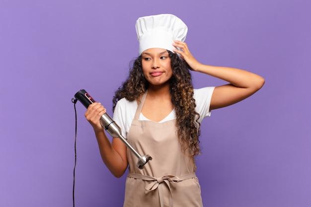 Jonge spaanse vrouw die zich verbaasd en verward voelt, hoofd krabt en opzij kijkt. chef-kok concept
