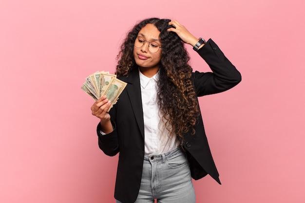 Jonge spaanse vrouw die zich verbaasd en verward voelt, hoofd krabt en opzij kijkt. dollar biljetten concept