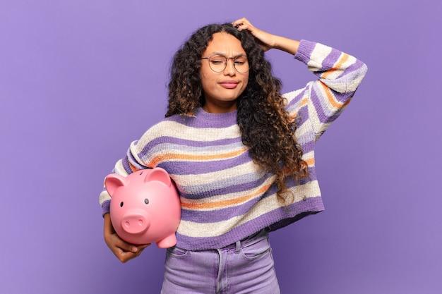 Jonge spaanse vrouw die zich verbaasd en verward voelt, hoofd krabt en opzij kijkt. spaarvarken concept
