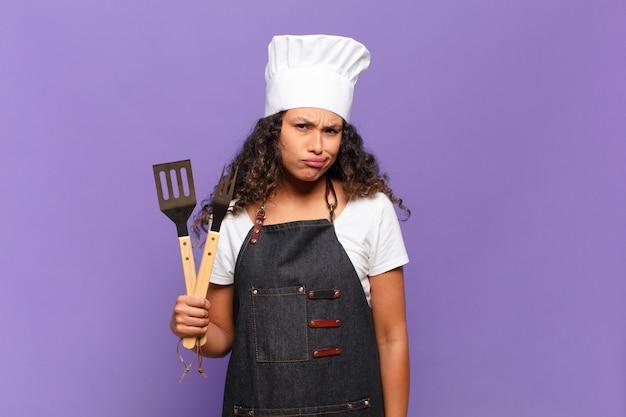 Jonge spaanse vrouw die zich verbaasd en verward voelt, met een domme, verbijsterde uitdrukking op zoek naar iets onverwachts. barbecue chef-kok concept