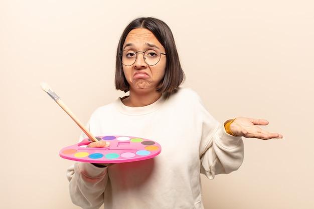 Jonge spaanse vrouw die zich verbaasd en verward voelt, onzeker is over het juiste antwoord of de juiste beslissing, probeert een keuze te maken