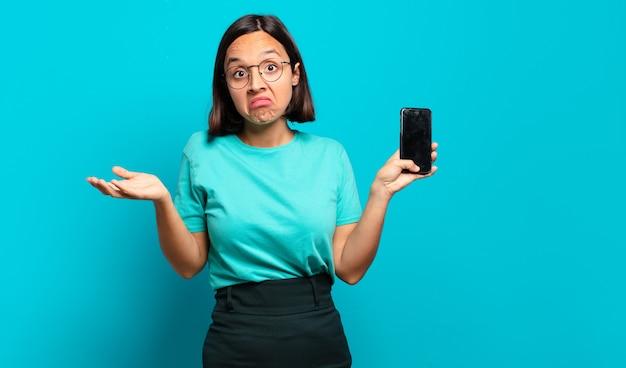 Jonge spaanse vrouw die zich verbaasd en verward voelt, twijfelt, weegt of verschillende opties kiest met een grappige uitdrukking