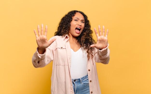 Jonge spaanse vrouw die zich verdoofd en bang voelt, bang voor iets angstaanjagends, met de handen vooraan open en zegt blijf weg