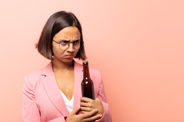 Jonge spaanse vrouw die zich verdrietig, boos of boos voelt en naar de zijkant kijkt met een negatieve houding, fronst van onenigheid