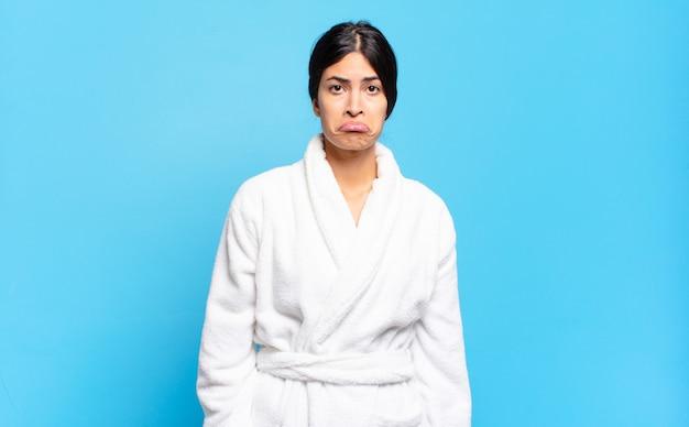 Jonge spaanse vrouw die zich verdrietig en gestrest voelt, van streek is vanwege een onaangename verrassing, met een negatieve, angstige blik. badjas concept