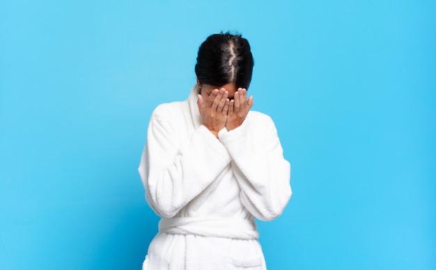 Jonge spaanse vrouw die zich verdrietig, gefrustreerd, nerveus en depressief voelt, gezicht bedekt met beide handen, huilend. badjas concept