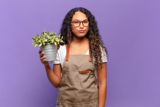 Jonge spaanse vrouw die zich verdrietig, overstuur of boos voelt en opzij kijkt met een negatieve houding, fronsend in onenigheid. tuin keeper concept
