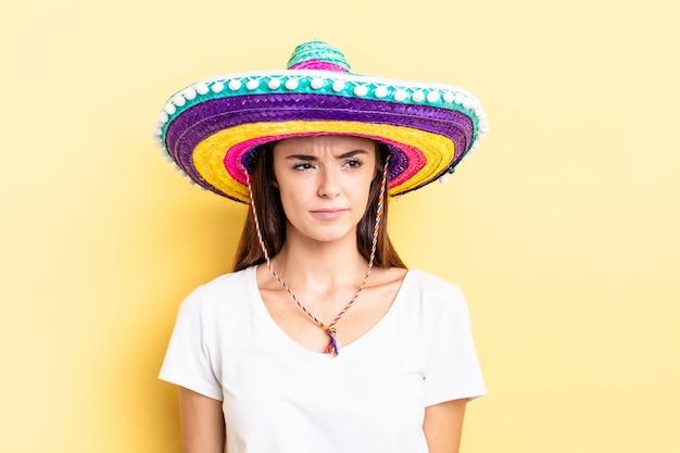 Jonge spaanse vrouw die zich verdrietig, overstuur of boos voelt en opzij kijkt. mexicaanse hoed concept