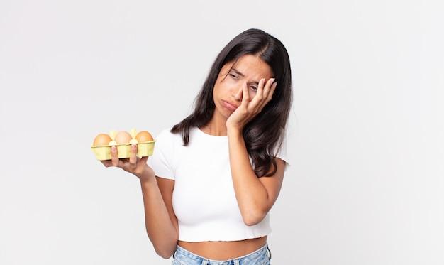 Jonge spaanse vrouw die zich verveeld, gefrustreerd en slaperig voelt na een vermoeiende bezigheid en een eierdoos vasthoudt