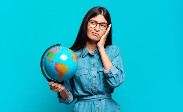 Jonge spaanse vrouw die zich verveeld, gefrustreerd en slaperig voelt na een vermoeiende, saaie en vervelende taak, gezicht met de hand vasthoudend. aarde planeet concept