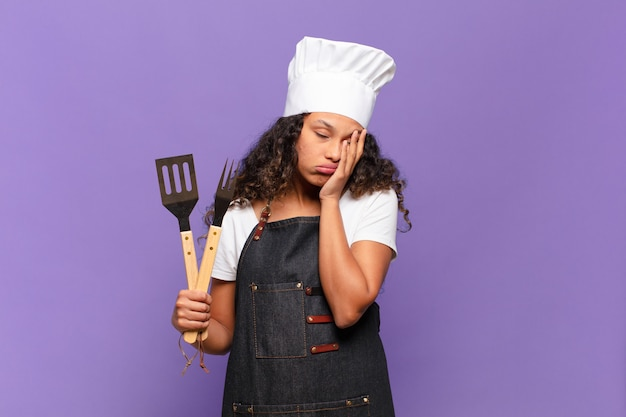 Jonge spaanse vrouw die zich verveeld, gefrustreerd en slaperig voelt na een vermoeiende, saaie en vervelende taak, gezicht met de hand vasthoudend. barbecue chef-kok concept