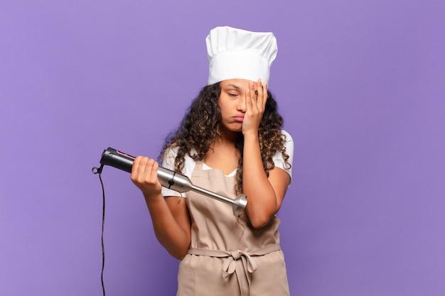 Jonge spaanse vrouw die zich verveeld, gefrustreerd en slaperig voelt na een vermoeiende, saaie en vervelende taak, gezicht met de hand vasthoudend. chef-kok concept