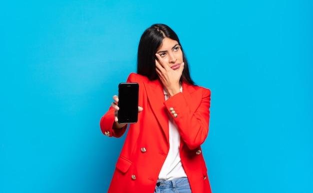 Jonge spaanse vrouw die zich verveeld, gefrustreerd en slaperig voelt na een vermoeiende, saaie en vervelende taak, gezicht met de hand vasthoudend. telefoon scherm kopieer ruimte